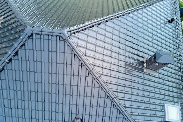 빛나는 세라믹 대상 포진으로 덮인 집 지붕 꼭대기의 근접 촬영.