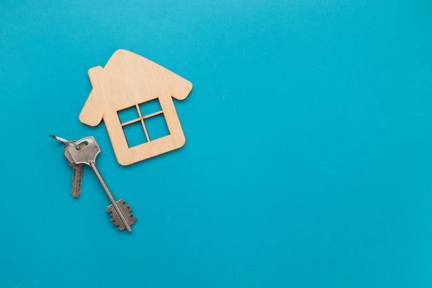 Макрофотография дома деревянные модели и ключи на синем