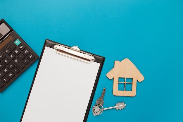 Макрофотография дома деревянные модели и ключи с заглушкой для текста на синем