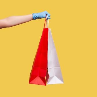 빨간색과 흰색 쇼핑백을 들고 보여주는 파란색 수술용 장갑을 끼고 인간의 손을 클로즈업합니다.