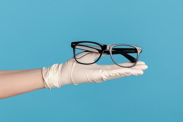 Крупный план человеческой руки в белых хирургических перчатках держа и давая черную рамку очков.