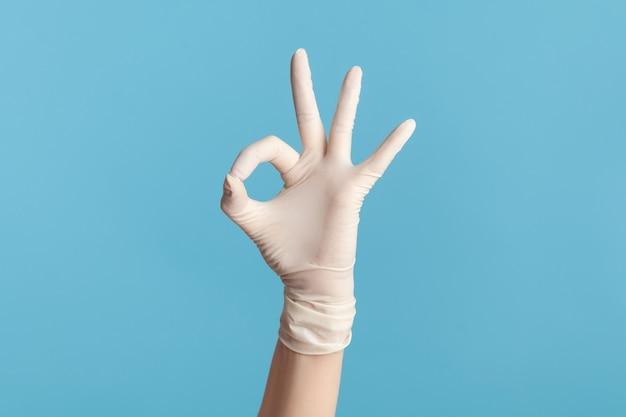 손가락으로 확인 표시 또는 숫자 3을 보여주는 흰색 수술 장갑에 인간의 손의 근접 촬영.