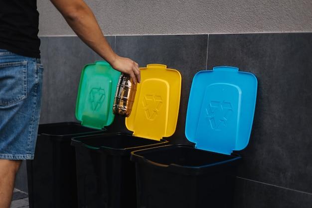 Крупным планом человеческая рука, бросающая пустую пластиковую бутылку из-под воды в мусорное ведро, дерево для мусора