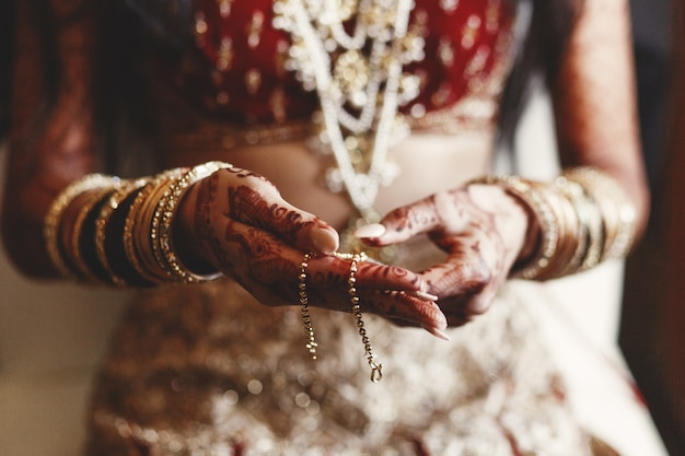 インドの花嫁の手のクローズアップ、メーディーで覆われ、保持