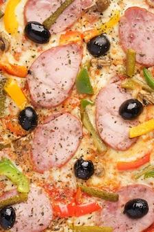 自家製ソーセージとイタリアンピザのクローズアップモッツァレラブルガリアペッパーオリーブ小さなきゅうりシャンピニオンオレガノ