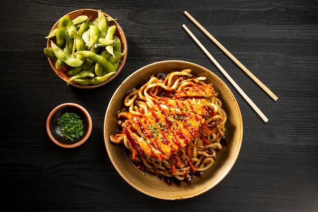 暗い面を上から見た、日本の麺とカリカリの鶏肉のクローズ アップ。