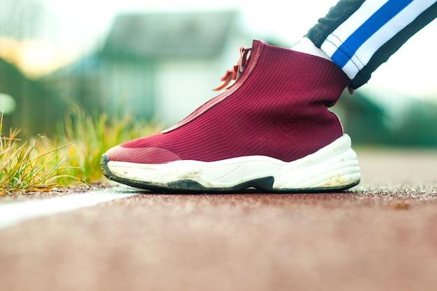 Крупный план ног бегуна в красных кроссовках.