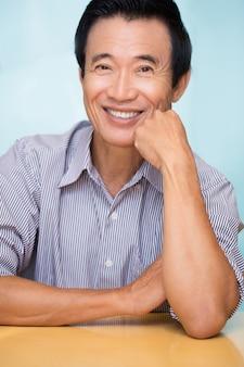 Closeup of Joyful Senior Asian Man at Table