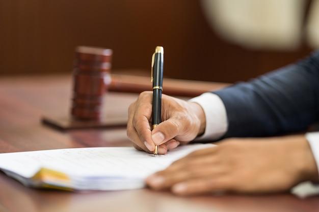 Крупным планом судьи деревянный молоток на звуковой блок и почерк человека на фоне