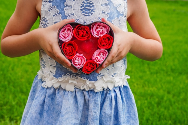 ピンクのハートに贈り物を持っている子供の手のクローズアップバレンタインデーの誕生日母の日フラットレイ愛のシンボルバレンタインデーの背景