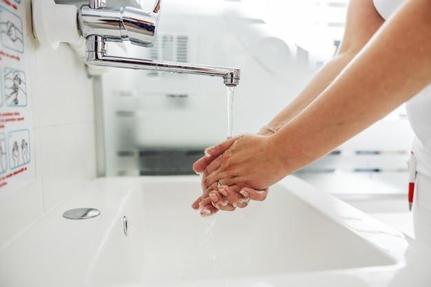Крупным планом лаборант, мыть руки, стоя в лаборатории.