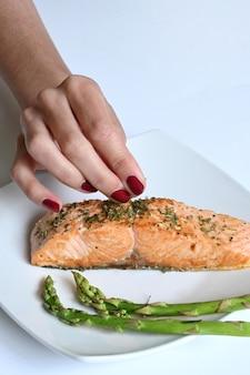 구운 연어 한 접시를 장식하는 라티나 여자 손 클로즈업