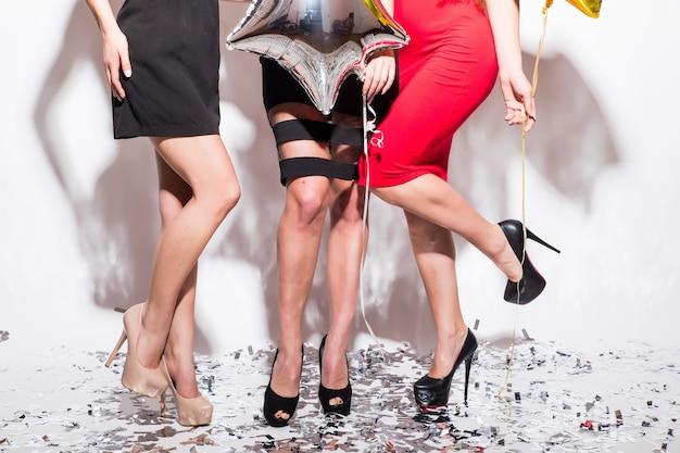 紙吹雪と白い背景の上のパーティーを持って床に立っている女性の足のクローズアップ