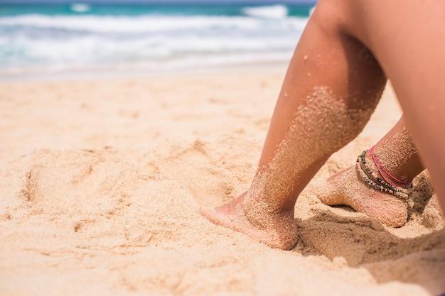 波と海と自然と砂を楽しんでビーチでリラックスした足の女性のクローズアップ-白人女性のためのヌーディズムと休暇の概念