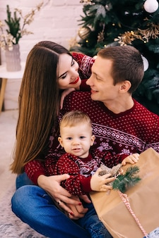 贈り物を持っている小さな男の子と両親のクローズアップは彼を抱きしめます。クリスマスツリーの背景に家族。