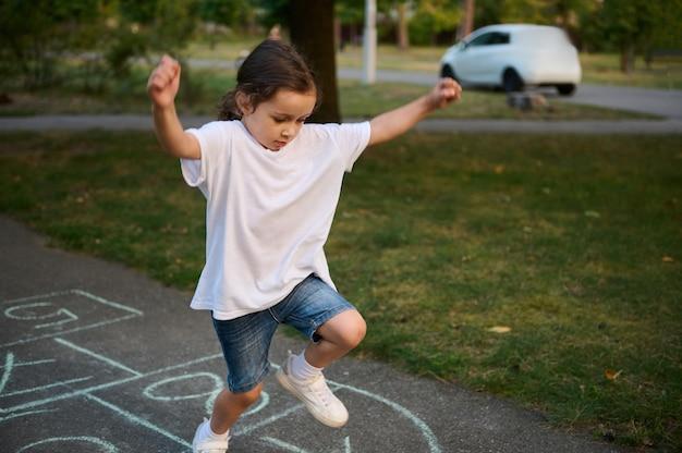 Крупный план маленькой кавказской девочки, играющей классики на асфальте. ребенок играет в классики на детской площадке на открытом воздухе в солнечный день. уличные детские игры по классике.