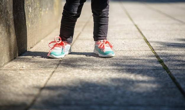 야외에서 운동화와 검은색 레긴스 훈련을 한 어린 소녀 다리 클로즈업