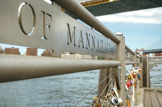 背景にニューヨーク市のイースト川とフェンスで愛の南京錠のクローズアップ