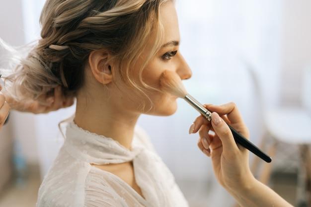 ブラシを使用して女性の頬にルージュを置くメイクアップアーティストのクローズアップ
