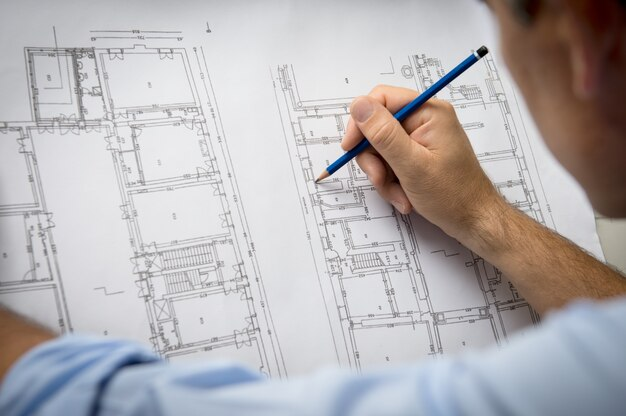 オフィスでの青写真に取り組んでいる男性の建築家のクローズアップ
