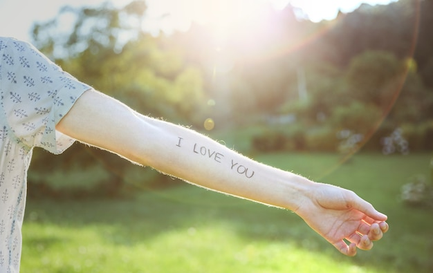 日当たりの良い自然の背景の上に皮膚に書かれたテキスト-私はあなたを愛しています-と男性の腕のクローズアップ