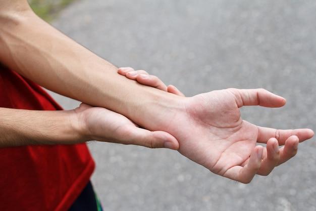 Крупным планом мужские руки держат ее болезненное запястье из-за упражнений
