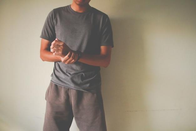 彼の痛みを伴う手首を保持している男性の腕のクローズアップ。