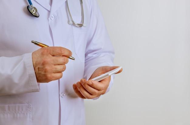 Крупным планом мужчина-врач руки делает заметки по рецепту в клинике