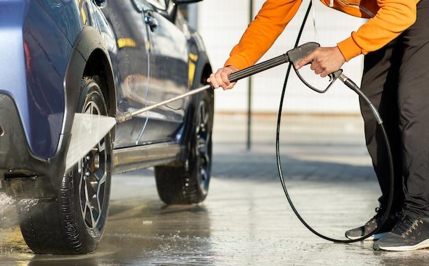 セルフサービス洗車で非接触型高圧ウォータージェットで車を洗う男性ドライバーのクローズアップ。