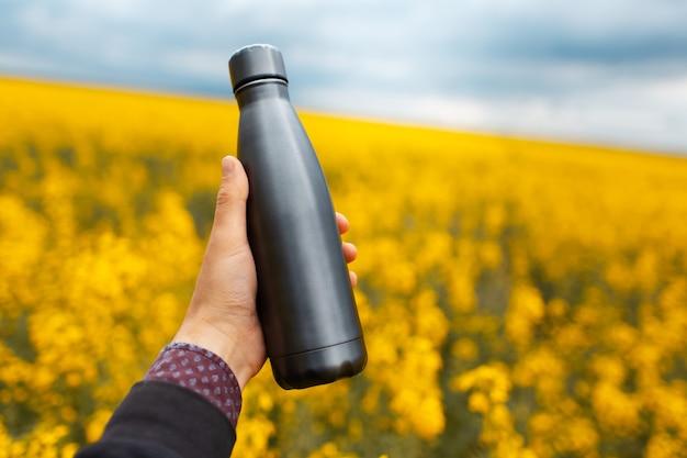 コピー スペースでぼやけた菜種畑の背景に暗い灰色の再利用可能な金属のボトルを持っている男性の手のクローズ アップ。