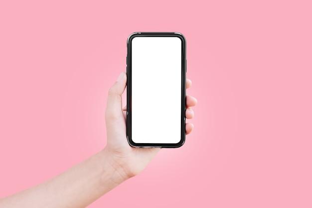 ピンク色の背景に分離されたモックアップでスマート フォンを持っている男性の手のクローズ アップ。