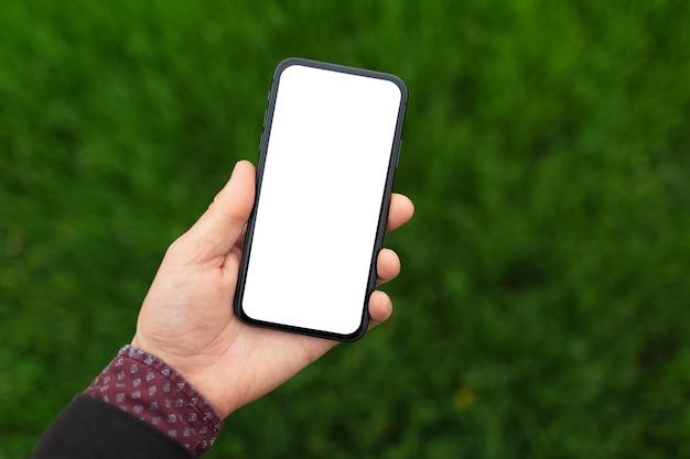 ぼやけた緑の芝生の背景にモックアップでスマート フォンを持っている男性の手のクローズ アップ。