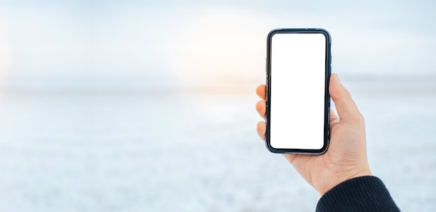 ぼやけた雪原の背景にモックアップでスマート フォンを持っている男性の手のクローズ アップ。日光効果。コピー スペースのあるパノラマ バナー ビュー。