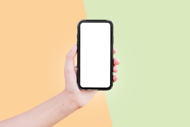 オレンジと緑の背景にモックアップ付きのスマートフォンを持つ男性の手のクローズアップ。パステル カラー。