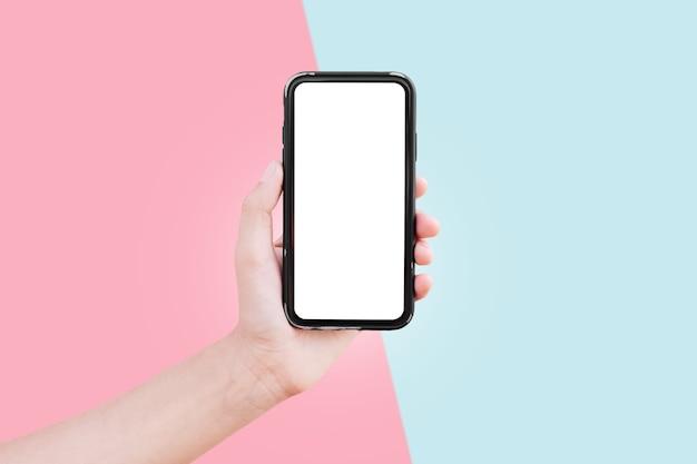 ピンクと青の背景にモックアップ付きのスマートフォンを持つ男性の手のクローズアップ。パステル カラー。