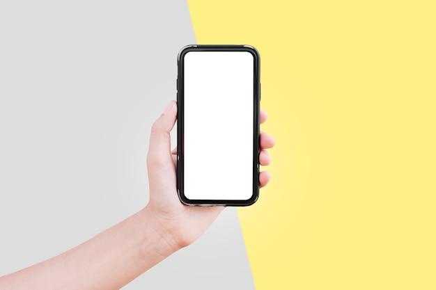 黄色と灰色の背景にモックアップ付きのスマートフォンを持つ男性の手のクローズアップ。 2021年の究極のグレーとイルミネーションの色。