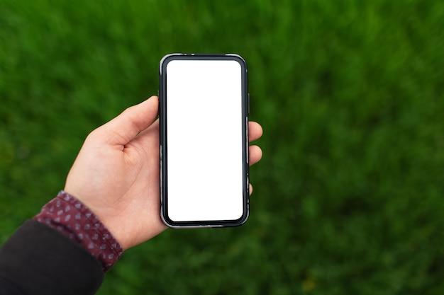 ぼやけた緑の芝生の背景に白いモックアップでスマート フォンを持っている男性の手のクローズ アップ。