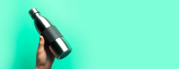 コピー スペースと緑の背景に鋼の再利用可能なサーモ ウォーター ボトルを持っている男性の手のクローズ アップ。パノラマ バナー ビュー。