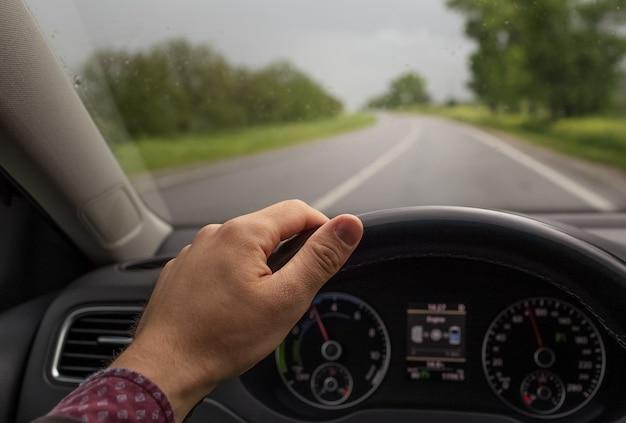 Крупным планом мужской руки, держащей рулевое колесо, за рулем автомобиля. фон размытой дороги в дождливый день. транспортная концепция.