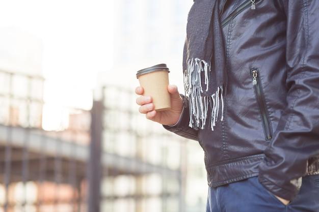 屋外の紙のコーヒーカップと男性の手のクローズアップ