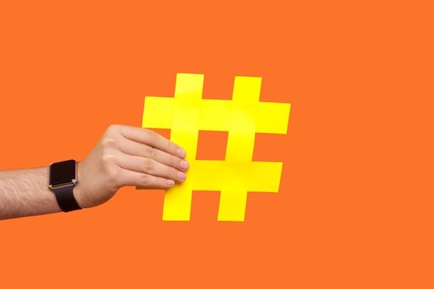 Крупный план мужской руки с наручными часами, держащими большой желтый знак хэштега, время для вирусных проблем и тенденций в социальных сетях, интернет-блогах. закрытый студийный выстрел изолирован на оранжевом фоне