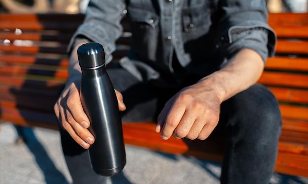 黒の鋼の再利用可能なサーモウォーターボトルを保持している男性の手のクローズアップ。