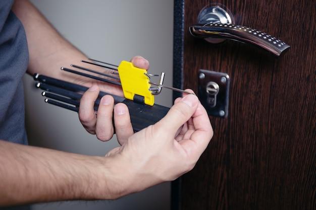 男性の手のクローズアップは、ドライバーで金属製のドアロックを修理またはインストールします。強盗保護の改善。
