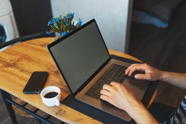 Крупный план мужских рук, набрав на клавиатуре современного портативного компьютера человека, работающего на смартфоне ноутбука и кофейной чашке на деревянном столе.