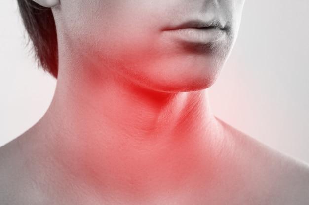 喉の痛みの症状を伴う男性の首のクローズアップ