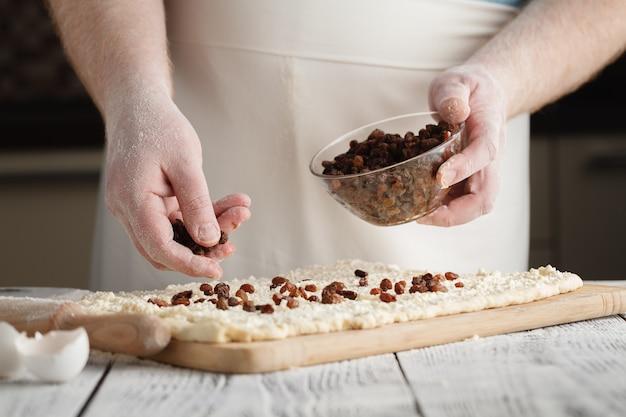 Крупным планом человека добавляет изюм в тесто.