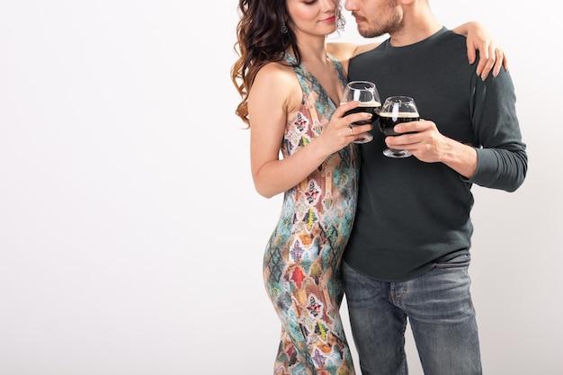コピースペースと白い背景の上の暗いビールのグラスで乾杯の男性と女性のクローズアップ
