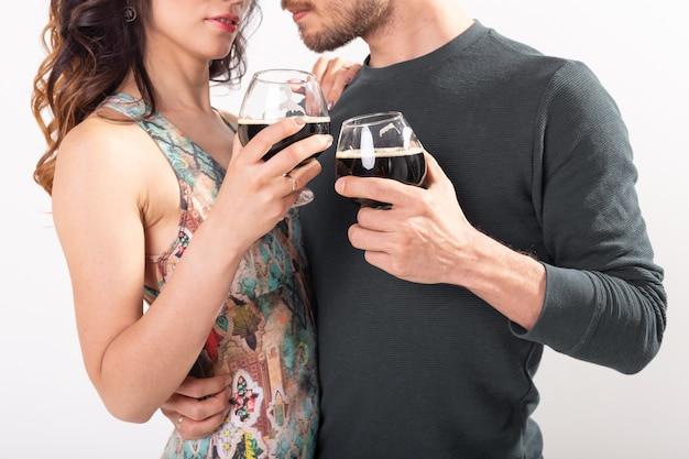 白い背景の上の暗いビールのグラスで乾杯の男性と女性のクローズアップ。