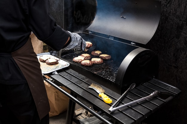 큰 그릴에 햄버거를 요리하는 사람의 근접 촬영