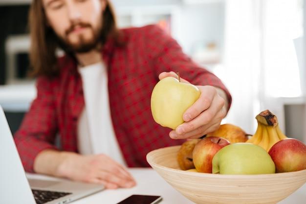 Крупным планом человека есть фрукты и с помощью ноутбука на дому